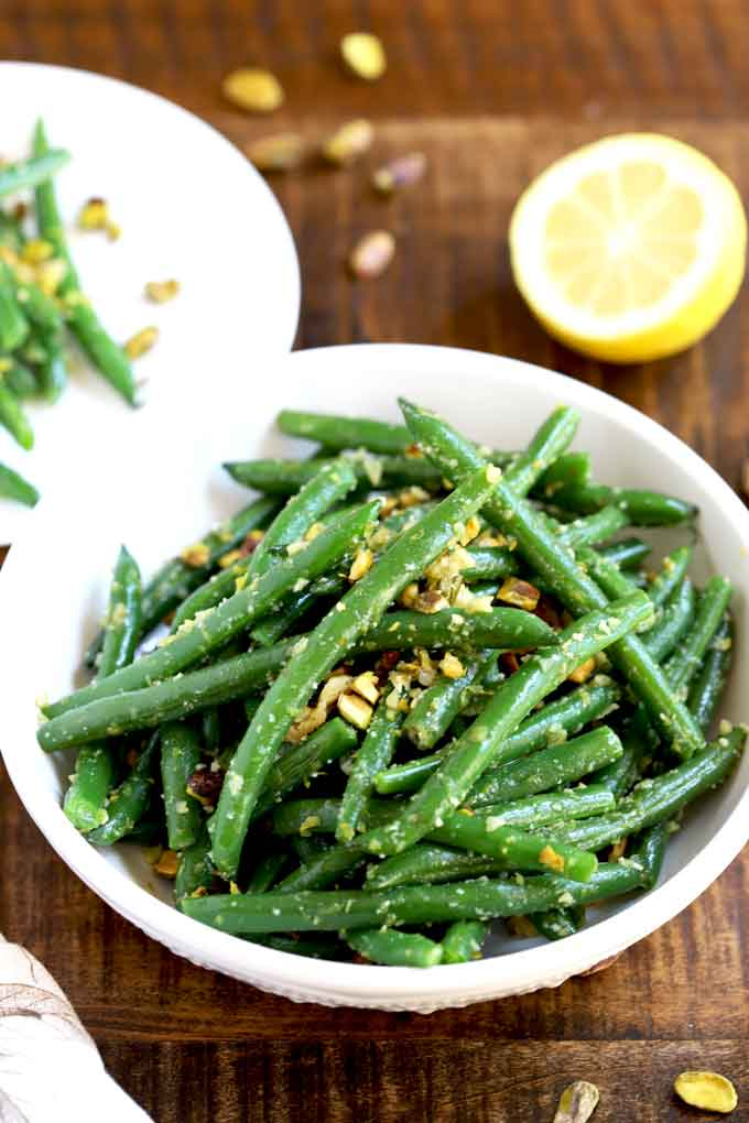 Sauteed green beans with garlic, lemon zest, Parmesan cheese and pistachios served in a white bowl.