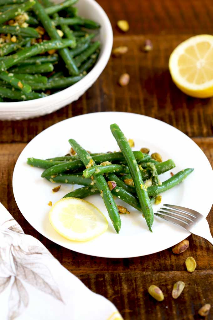 A sering of sauteed green beans on a white plate.