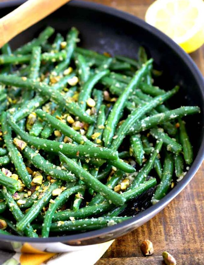 Close up view of sauteed green beans topped with pistachios and Parmesan in a skillet
