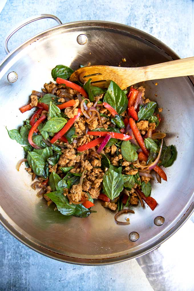 Thai Chicken Basil stir fried in a wok.