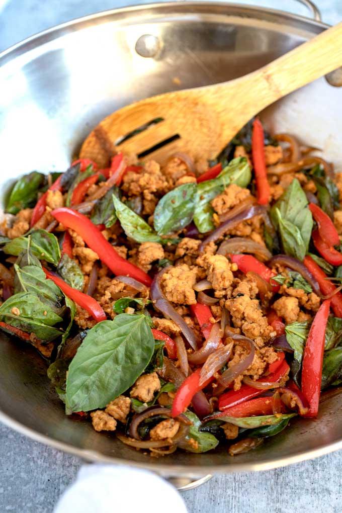 Thai Chicken stir frying in a wok.