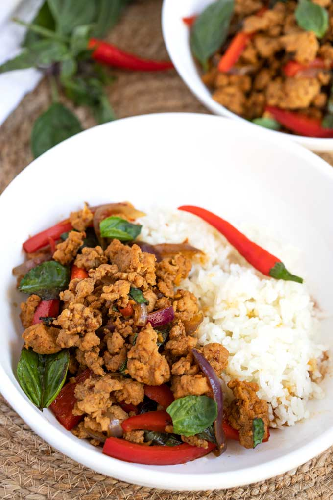Mouthwatering Thai Basil Chicken served with rice in a white bowl.