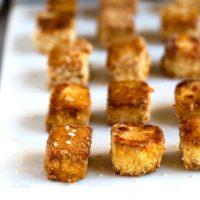 Crispy golden brown tofu on a white serving board