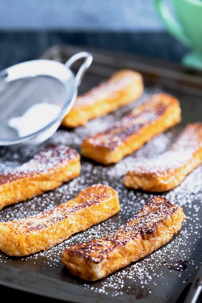 Sticks of golden cinnamon French toast on a baking sheet