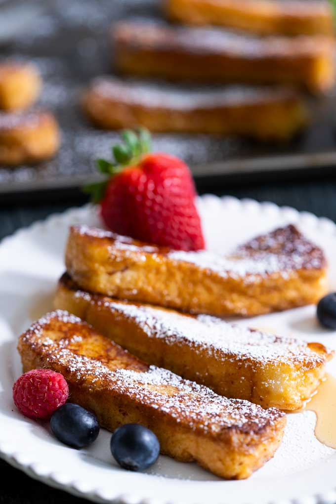 Golden brown French toast sticks sprinkled with powdered sugar and garnished with fruit on a white plate.