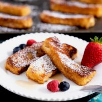Golden brown rich and delicious French toast sticks on a white plate.