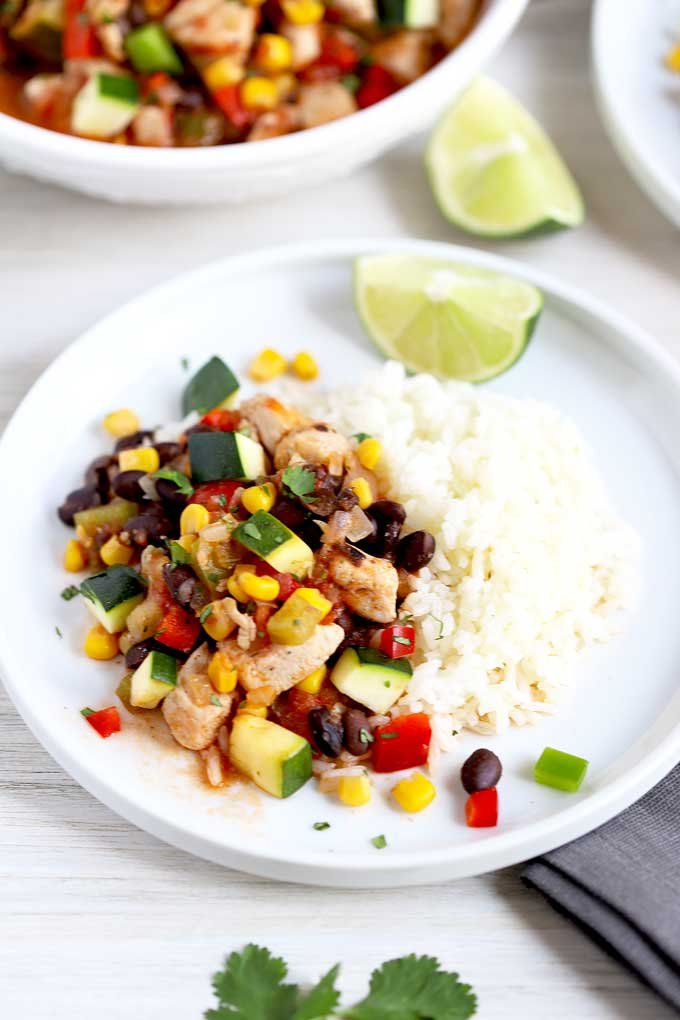 Hearty Chicken Stew with corn and black beans served with white rice on a white plate.