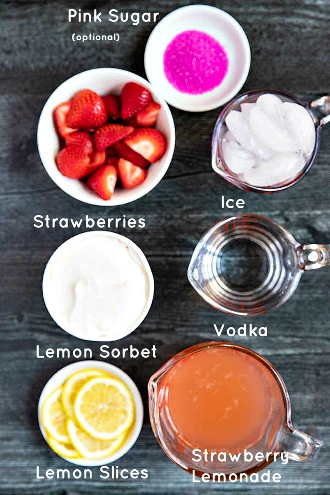 Ingredients to make refreshing strawberry vodka cocktail set on a dark surface