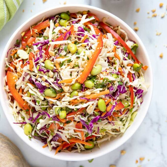 Top view of a white salad bowl filled with Asian slaw.