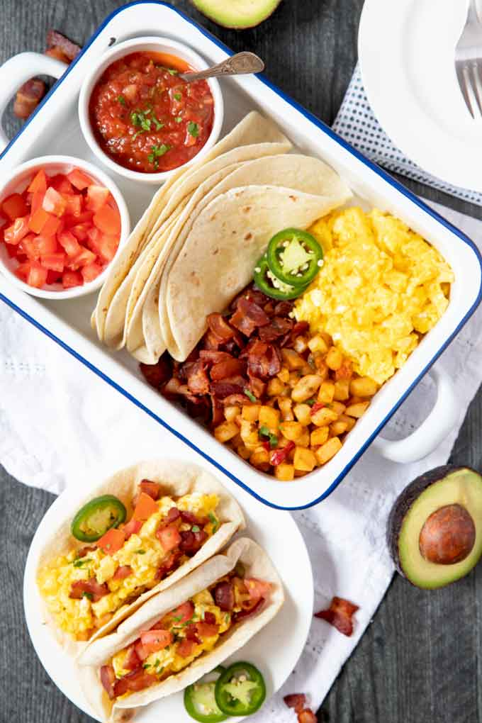 A tray filled with tortillas and sll the cooked tacos ingredients and toppings.
