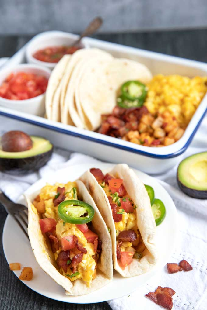 Two breakfast tacos filled with potatoes, scrambled eggs and bacon next to a tray fill with scrambled eggs, potatoes, tortillas, bacon, salsa and tomatoes.
