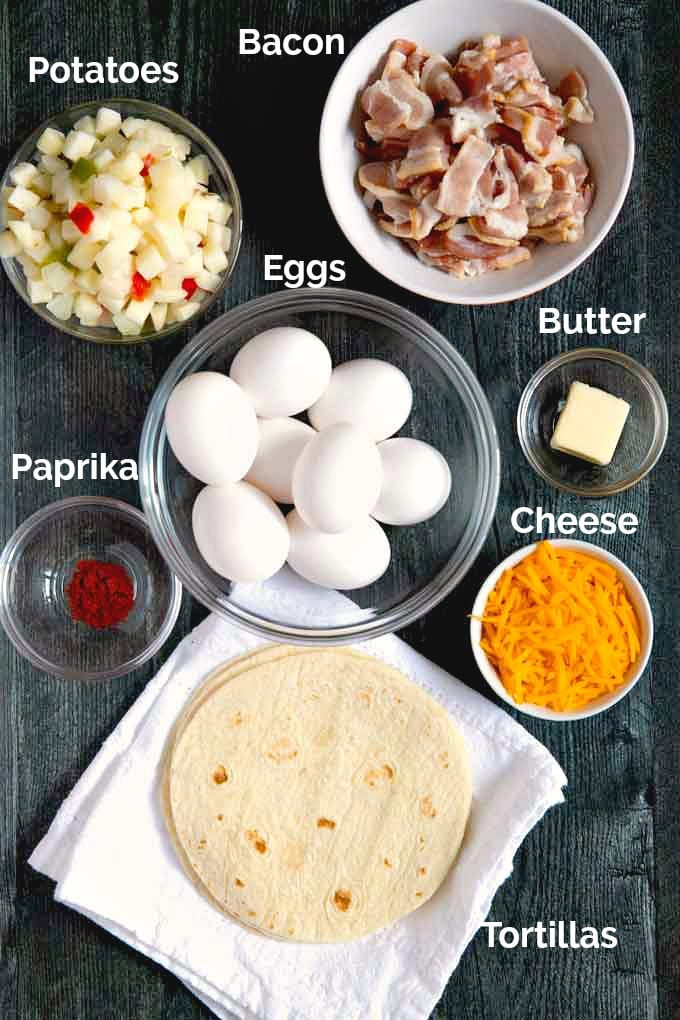 Ingredients to make this breakfast recipe on a dark surface. Eggs, potatoes, cheese, bacon, paprika, butter, tortillas.