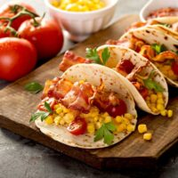 Breakfast tacos with bacon on a wooden board