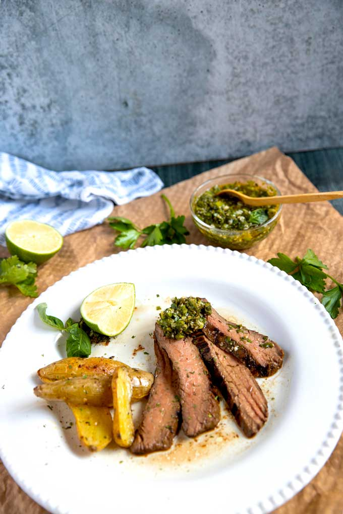 A few sliced of grilled steak topped with chimichurri served with golden potatoes on a white plate.