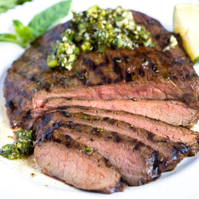 Grilled steak sliced and top with Asian chimichurri on a white plate.