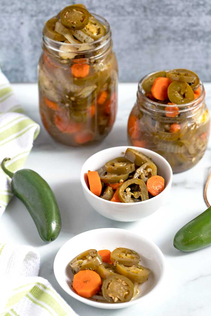 Several jars and containers filled with pickled carrots, onions and jalapenos.