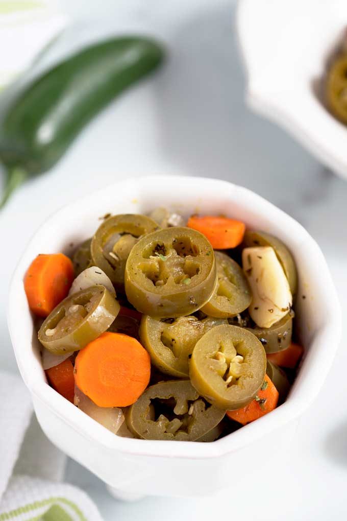 A small bowl with Mexican style pickled peppers and carrots.