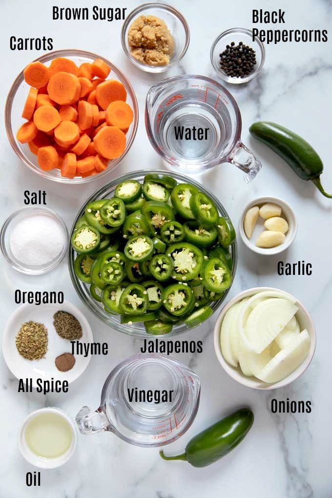 Ingredients to make pickled jalapenos on a white marble surface.