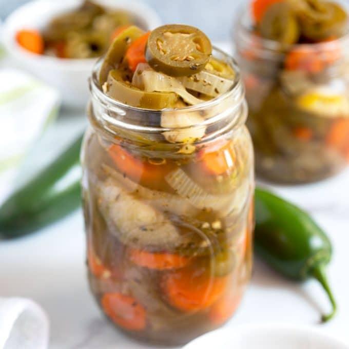 A jar of pickled jalapenos set among other jars.