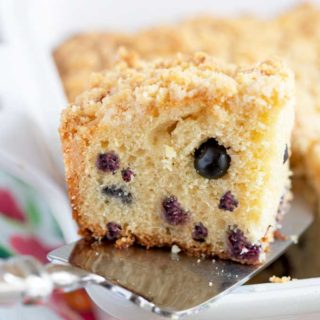 A piece of coffee cake getting lift with a cake server from a baking dish.
