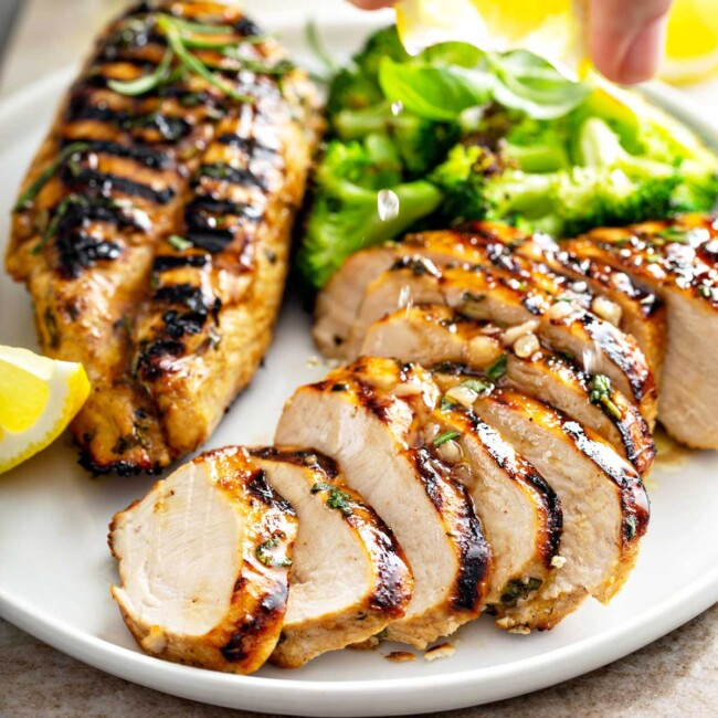 Grilled chicken Breast - lemon Blossoms: sliced chicken breast served on a white plate with broccoli.