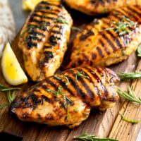 Grilled chicken Breast - lemon Blossoms: Grilled chicken breast on a wooden board.
