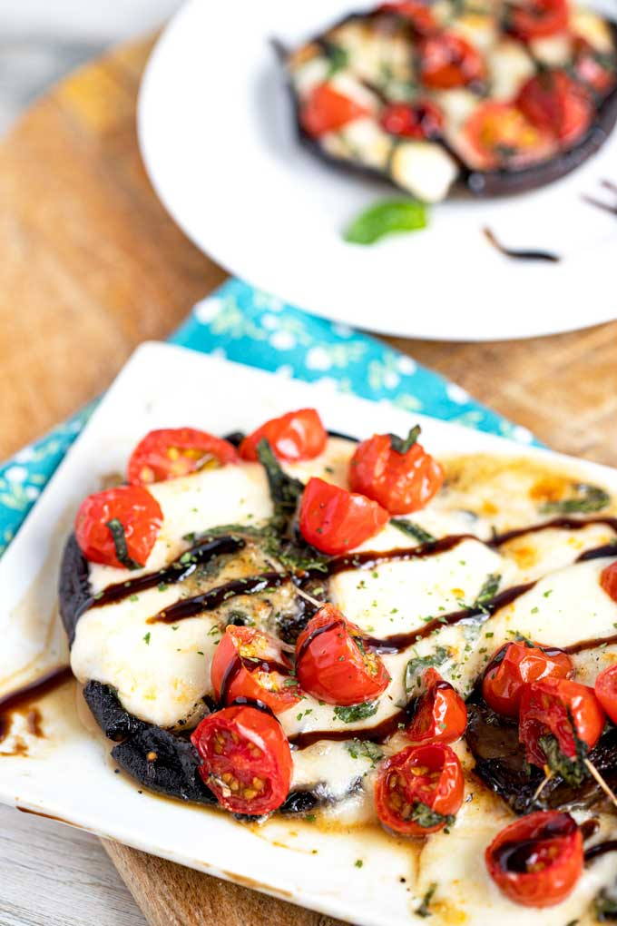 Melted mozzarella and tomatoes bursting stuffed in a mushroom cap