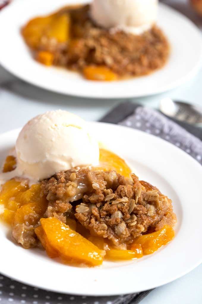 Peach crisp with ice cream on the side on a white plate.