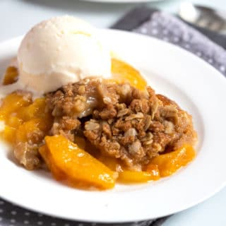 Peach dessert with crumbly topping on a white plate served with vanilla ice cream.