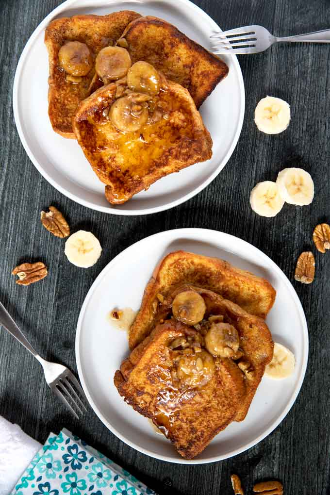 Two plates with bananas foster French toasts