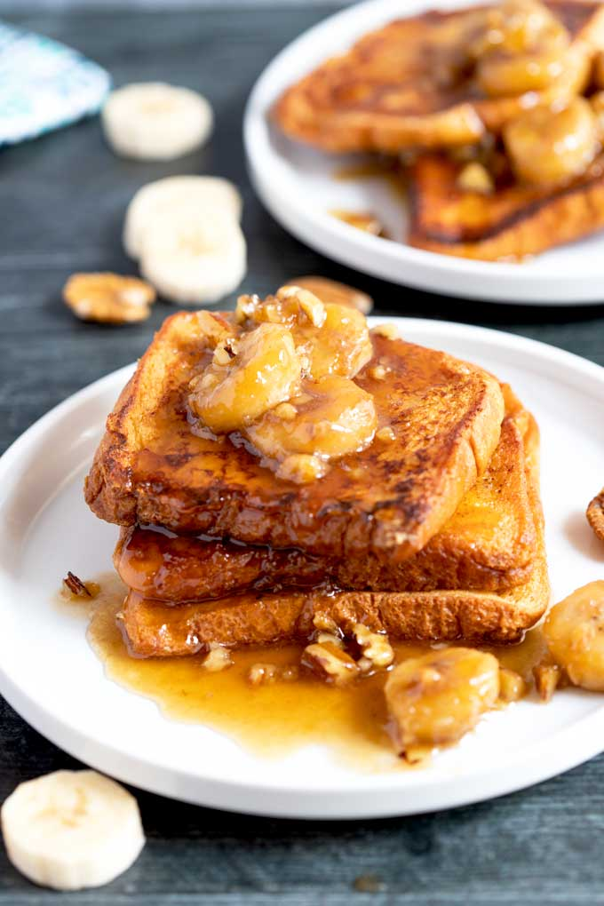 Brioche French toast with banana topping on a white plate