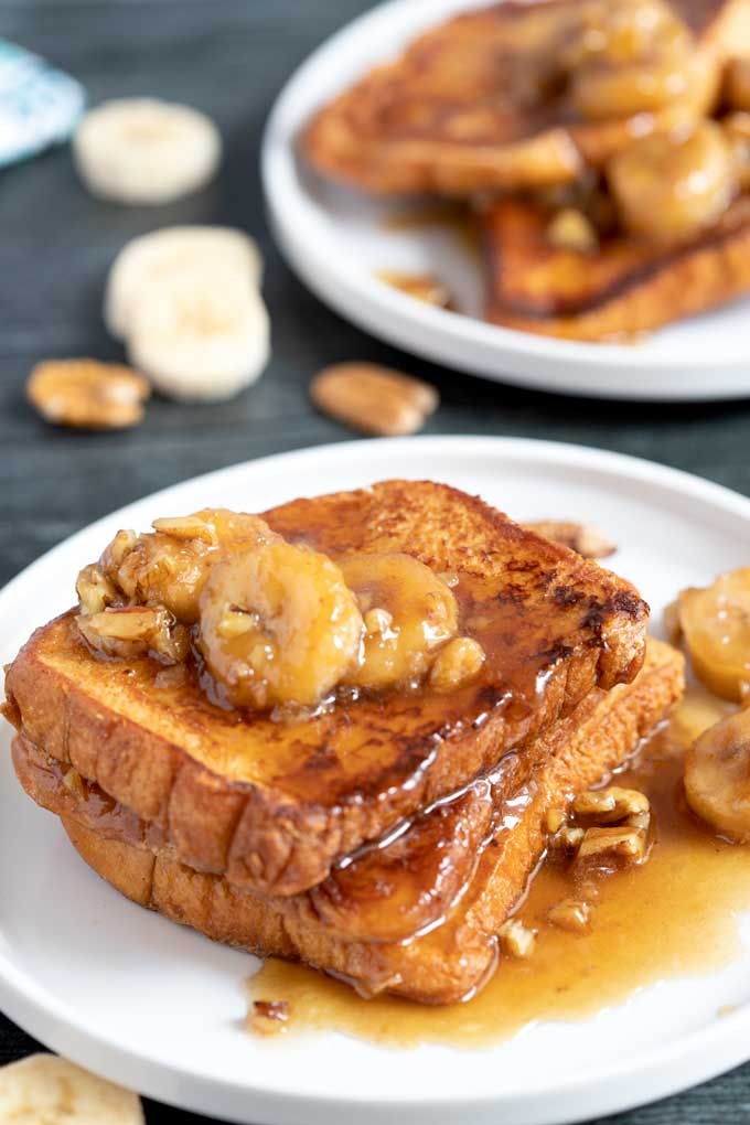 Three slices of French toast with bananas and pecans on a white plate