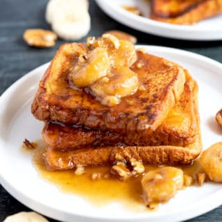 Banana Foster topping served over French toast on a white plate.