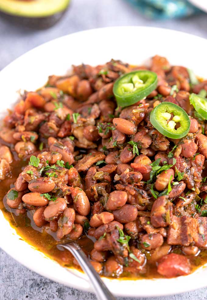 A big bowl of pinto beans Mexican style topped with jalapeno slices.