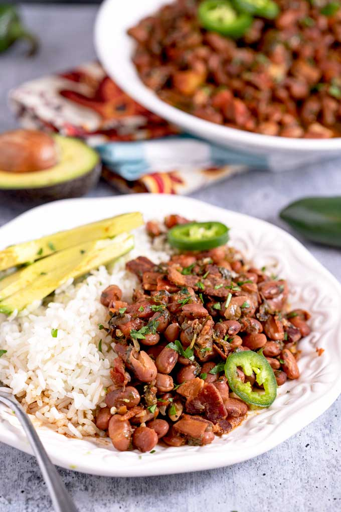 Charro beans or Frijoles Charros in Spanish, served with rice and avocado slices.