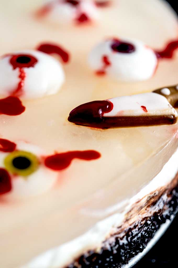Close up of the cheesecake jello layer with a bloody candy knife and bloody candy eyeballs