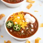 A bowl of chili with assorted toppings.