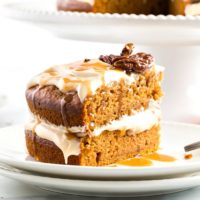 Sliced pumpkin cake with caramel cream cheese frosting on a white plate