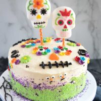 Dia De Los Muertos Cake with Sugar Skull Topper on a cake stand.