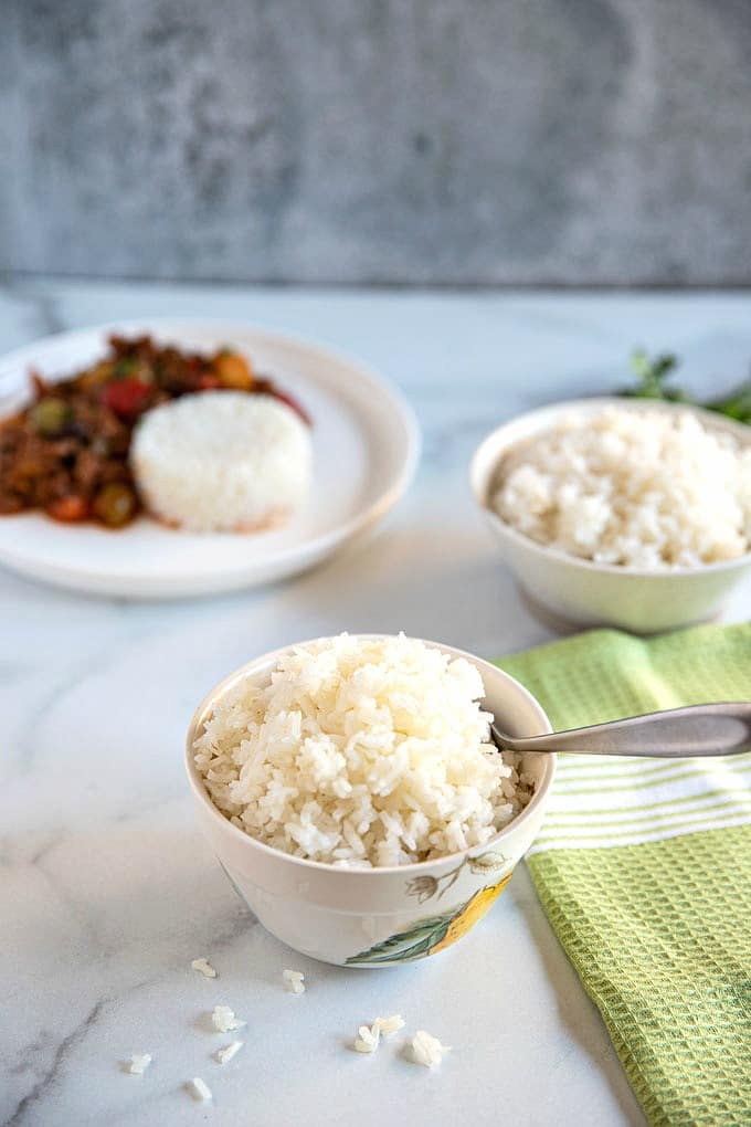 Bowls of cooked white rice on a light surface. rice on a