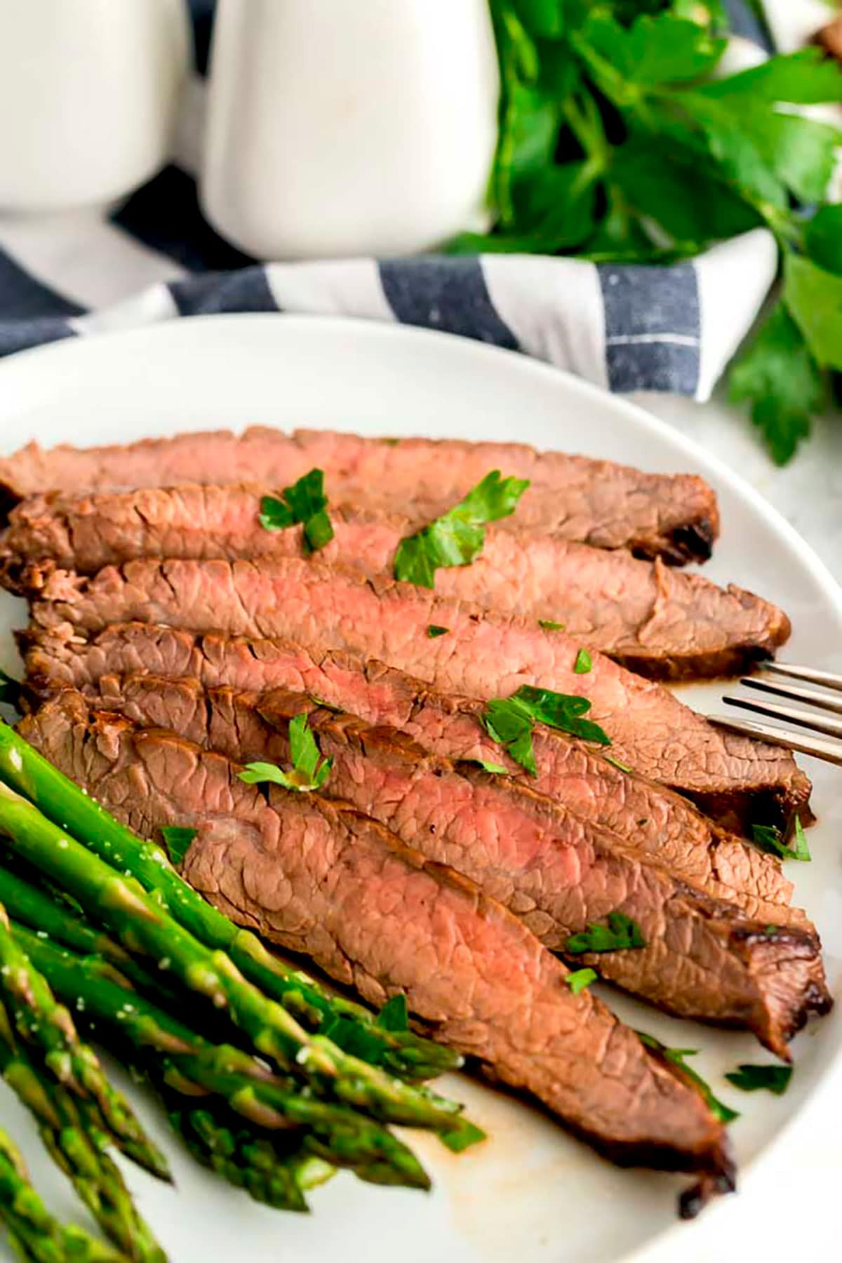 London broil sliced and served with asparagus.