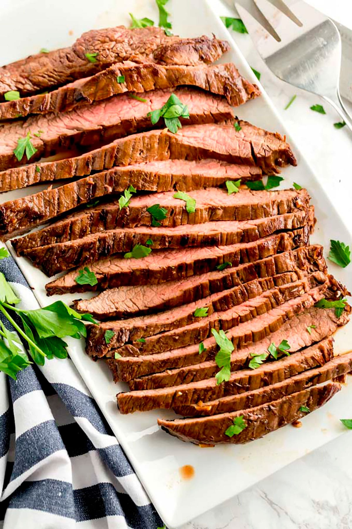 Sliced Juicy and tender London Broil fank steak on a white platter.