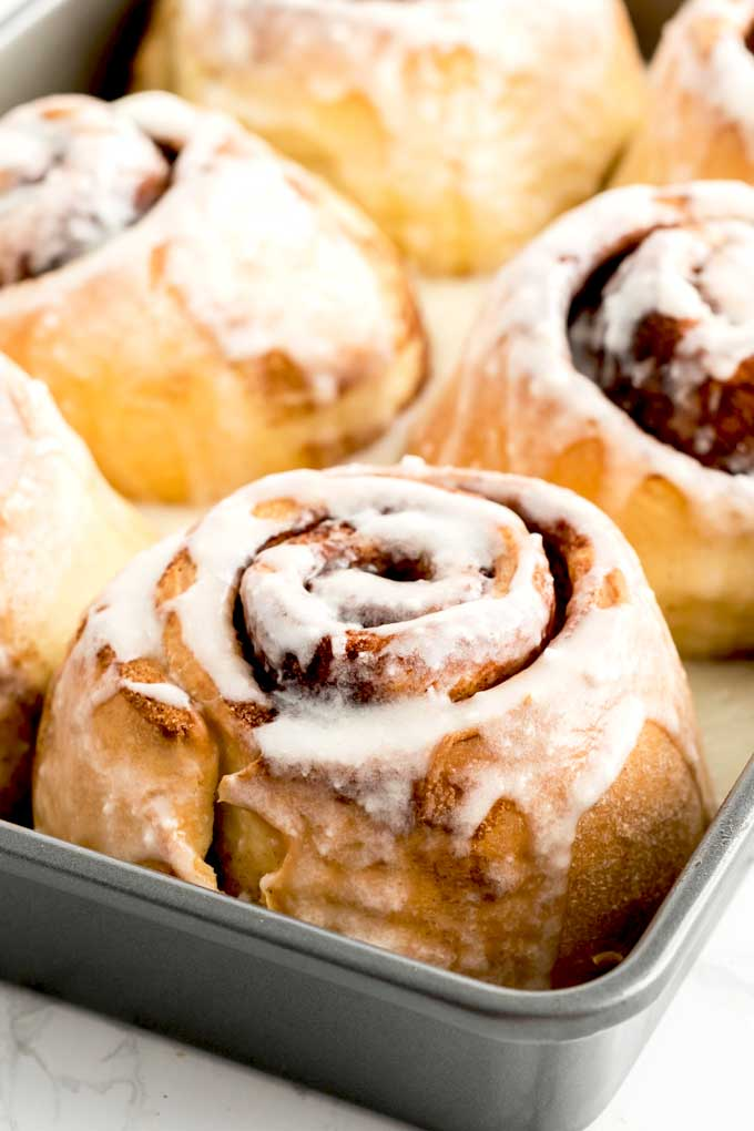 Close up of baked cinnamon buns in a baking pan.