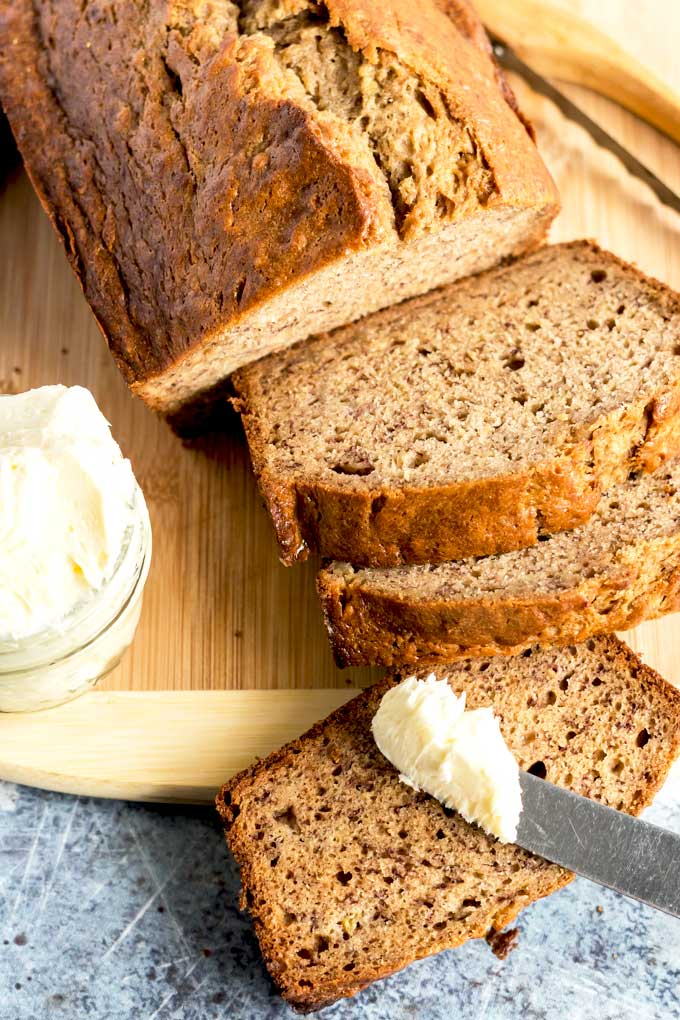 loaf of banana bread sliced served next to a small container of whipped butter,