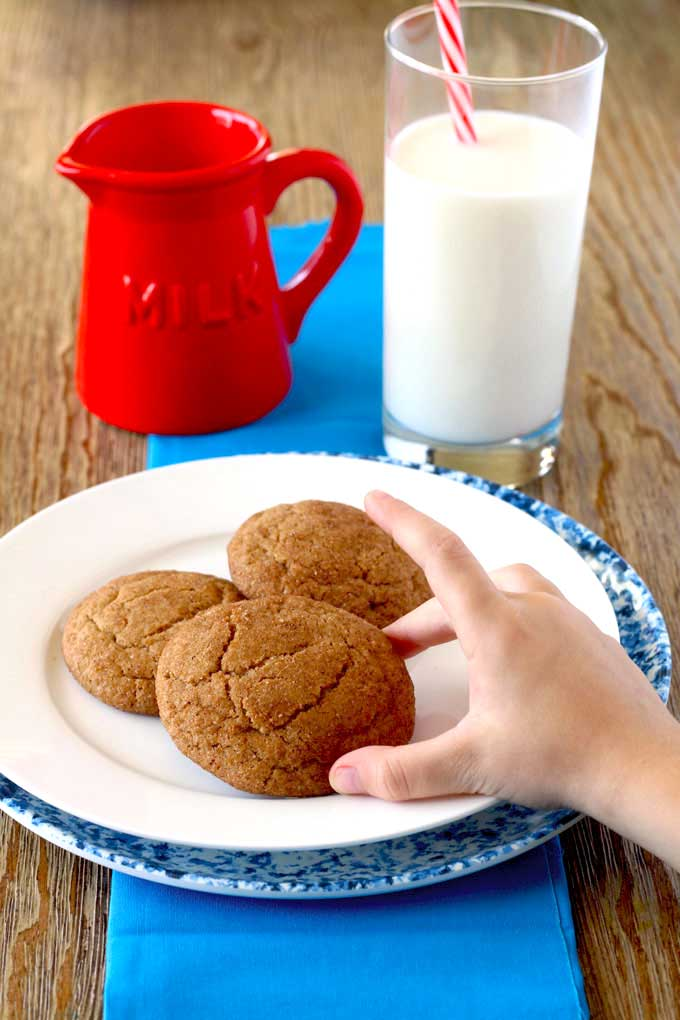 Child reaching for a snickerdoodle cookie.