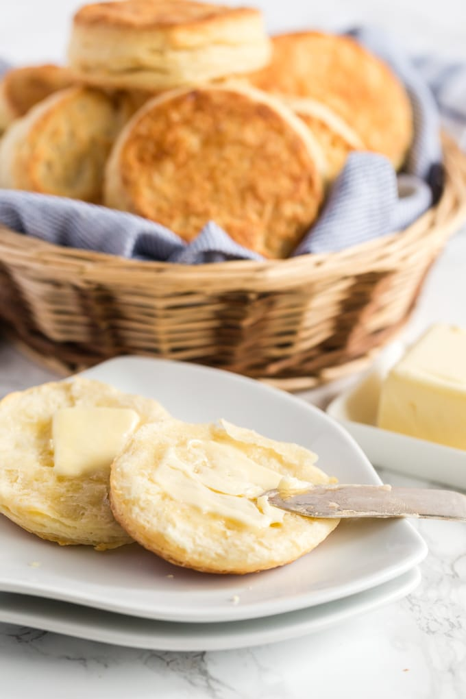 Biscuits slathered with butter on a white plate.