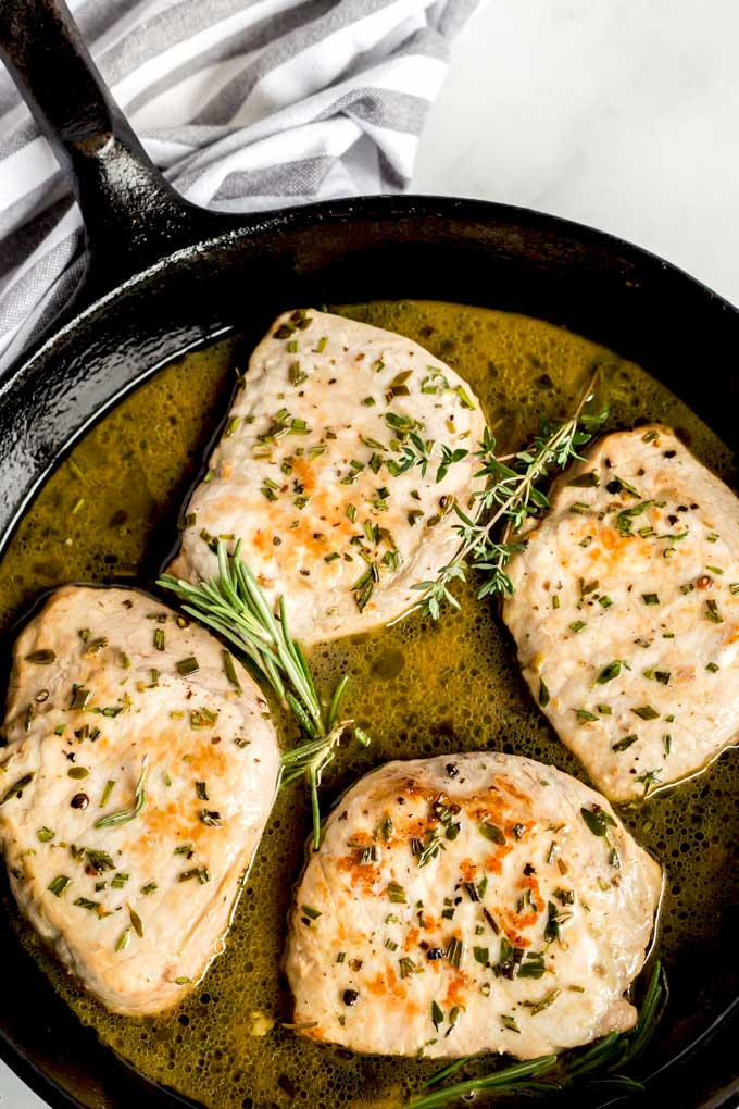 Herb crusted pork chops in a cast iron skillet