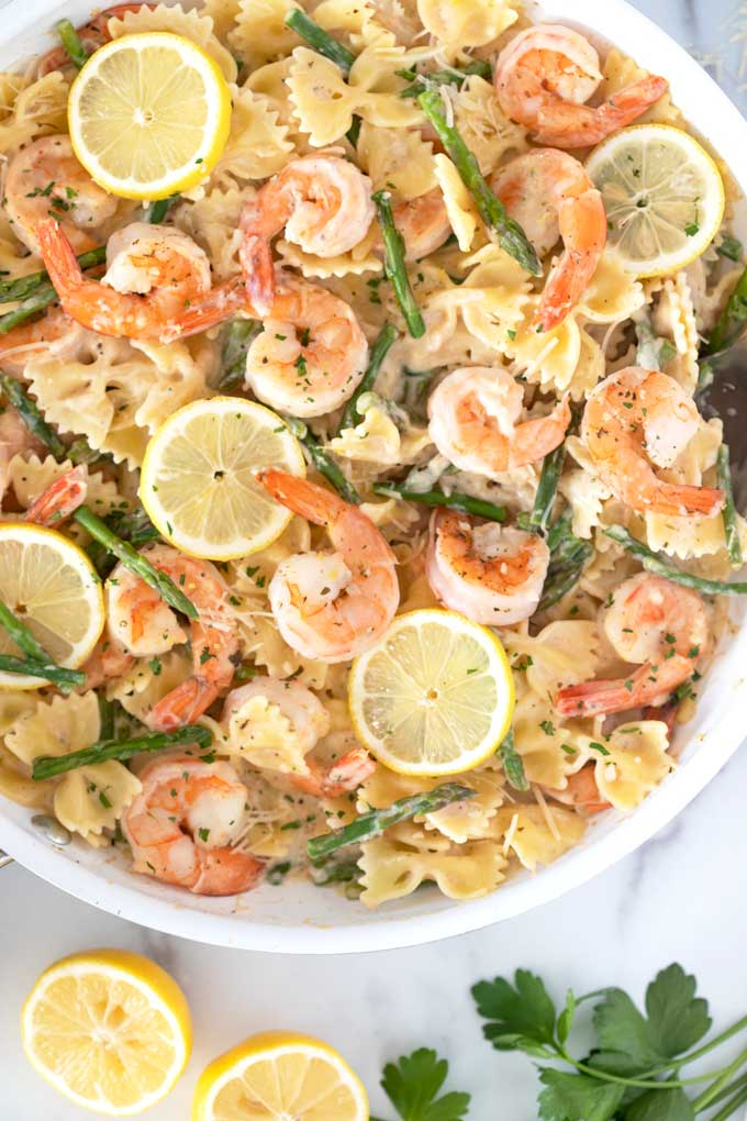 Skillet filled with creamy shrimp and asparagus Parmesan pasta.