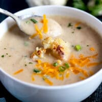 Creamy Cauliflower Soup topped with roasted cauliflower, shredded cheese and scallions