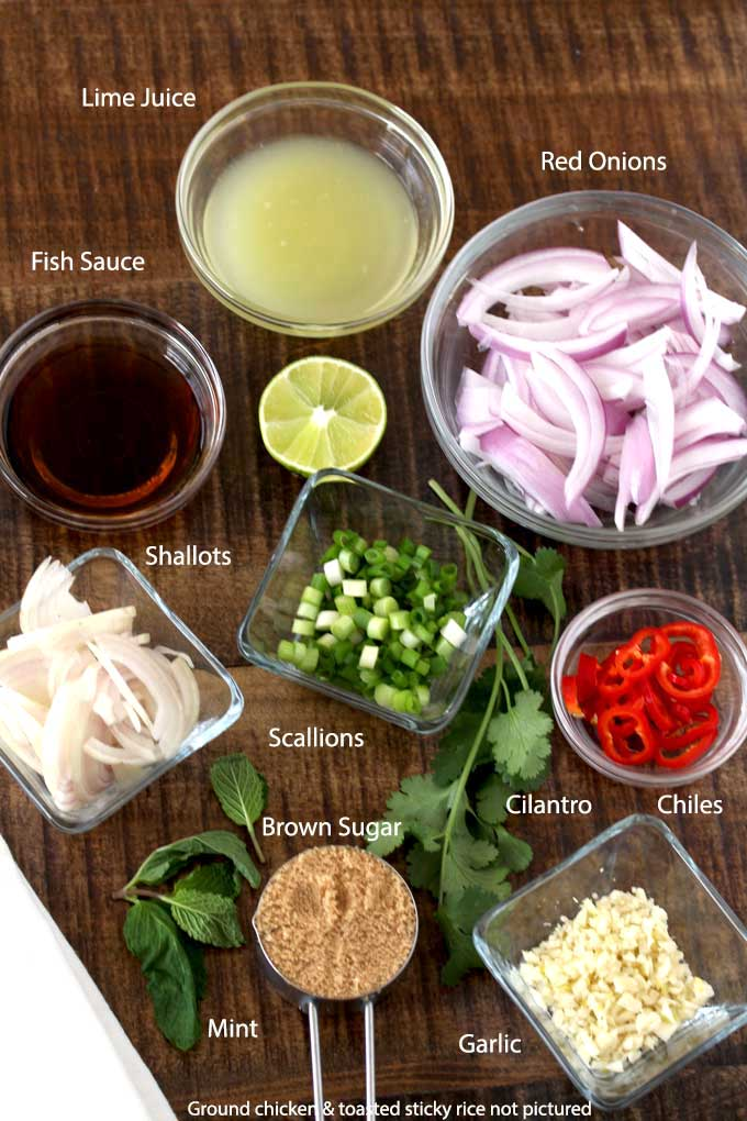 Chicken larb recipe ingredients on a wooden surface.